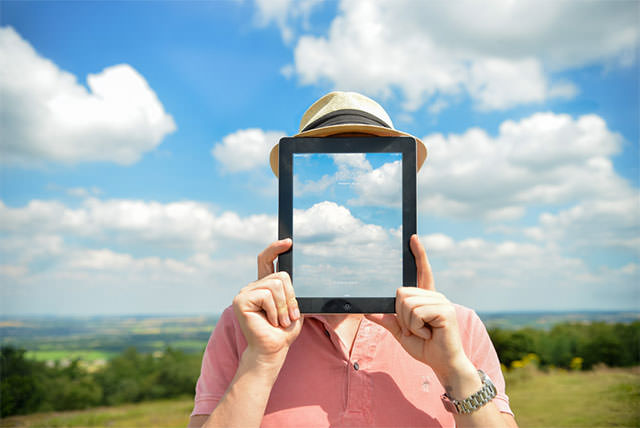 Concept-Of-Man-Holding-iPad-In-Front-Of-Face-With-Clouds-And-Countryside