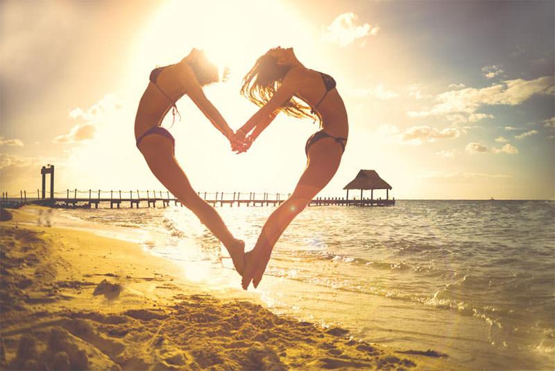Gilrs-On-Beach-Jumping-To-Make-Cute-Love-Heart