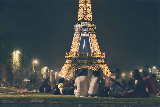 Group-Of-People-Socialising-In-Front-Of-Eifel-Tower-At-Night