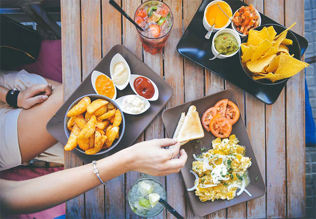 Womans-Hand-Taking-Food-From-Cafe-Table-With-Dips-And-Drinks